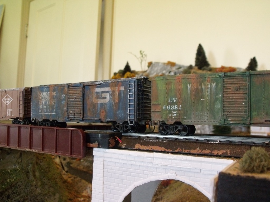 The two boxcars closest are both scavenged from cheap train sets. With some weathering, they look pretty decent. They may not hold up on close scrutiny but in a passing train, it doesn't matter.