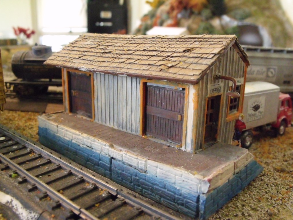 A Cheap Bachmann train set building with new paint, a new roof of construction paper shingles, and cinder-block loading dock made from an old kit.